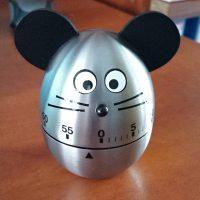 Nerezová oválná minutka tvaru vejce s černými čísly jako časomírou v dolní části, černým nosem, fousky, dvěma černobílýma očima a černými vystupujícími oušky na hlavě, která mají imitovat myš, na červeno-hnědém podkladu v interiéru.