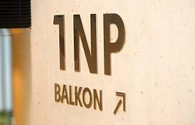 Označení patra 1 NP, text balkon a šipka, vyřezáno z nerezu, nalepeno na betonové zdi
