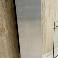 Nerezový totem před béžovou mramorovou zdí, gravírovaný nápis NA PŘÍKOPĚ 14, OBJEKT A a čísla podlaží, bílá mramorová dlažba