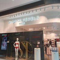 Prosklená prodejna spodního prádla v prostředí obchodního domu, vlevo i vpravo další obchody, za sklem dvě figuríny ve spodním prádle, nad levou bílá stěna s nápisem SIMONE PÉRÉLE PARIS, v prodejně stojany se spodním prádlem