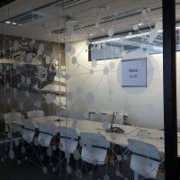 Skleněná stěna zasedací místnosti, polepená řezanou bílou grafikou s motivem kruhů a přímek, za ní konferenční stůl a židle, fototapeta na stěně