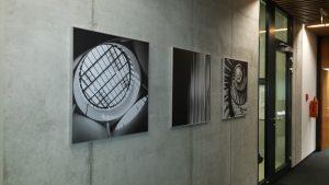 Tři černobílé fotografie jako obrazy ve stříbrných rámech na betonové stěně, v pozadí prosklené dveře s černým rámem