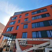 Oranžová budova s černě lemovanými okny zdálky, uprostřed 3D šedo-modré logo a nápis team IT, v popředí bílý montážní stroj, v pozadí modrá obloha