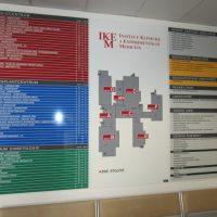 Velký orientační modulový systém IKEM, uprostřed plán budovy, po stranách značení částí, přimontováno na bílé zdi chodby