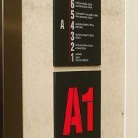 Dvě černé čtvercové desky s bílými a červenými gravírovanými texty na světlé zdi, popis pater 1–6 budovy A1