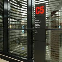 Černý kovový sloupek s hliníkovou deskou, červené plastické označení C5, bílý text jako navigace k oddělení Metrostav Development, skleněné dveře s černým rámem, žaluzie