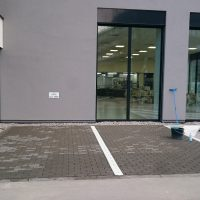 Bílé linky z epoxidových podlahových barev jako označení parkovacích míst před budovou, šedá budova s prosklenými dveřmi, nářadí potřebné pro provádění malby