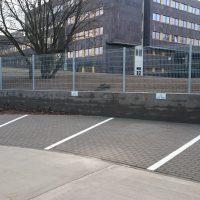 Bílé linky a piktogram handicapované osoby z epoxidových podlahových barev jako označení parkovacích míst u zdi s plotem, v pozadí šedá administrativní budova