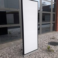 Bílý LED prosvícený panel s černým dibondovým rámem, připevněn železným soklem na oblázkový štěrk, skleněná budova