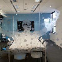 Pískovaná folie s motivem plavce, kruhů a přímek nalepená na skleněné stěně zasedací místnosti se stolem, židlemi a obrazovkou