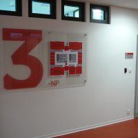 Informační tabule z plexiskla, červené označení 3. NP a orientační plán, přimontováno na bílé zdi chodby, červená podlaha, okýnka, šedé dveře