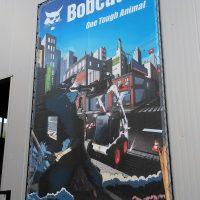 Velkoplošný banner vyvázaný v rámu na stěně budovy, reklama Bobcat s ilustrací malého bagru městské zástavbě