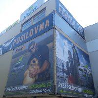 Roh budovy, vpravo i vlevo pokryt bannerem s reklamou na rybářské potřeby, vpravo šedá část budovy, nahoře další část budovy a jiné reklamní bannery