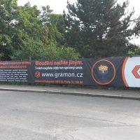 Exteriér, v popředí asfaltová silnice, v pozadí chodník, za ním na plotě banner, v pozadí stromy