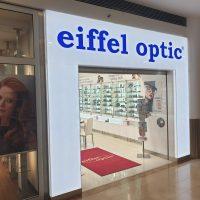 Podsvícená bílá brána do prodejny nahoře s modrým nápisem eiffel optic, v prostředí nákupního centra, uvnitř prodejny vitríny s produkty, na zemi červený koberec