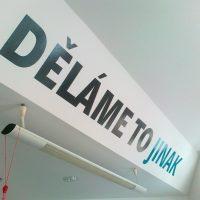Slogan DĚLÁME TO JINAK vyřezaný z černé a modré plotrové folie nalepený na bílé stěně u stropu, svítidlo