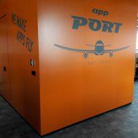 Rohové příčky v interiéru polepené oranžovou plotrovou folií s šedým logem App PORT a sloganem WE MAKE APPS FLY, v pozadí muž na kancelářské židli
