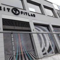 Černé 3D logo FITLAB na šedé stěně budovy, okna polepená barevnou děrovanou folií