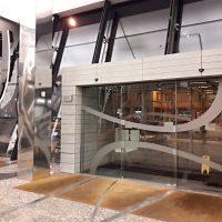 Skleněné dveře s automatickým otevíráním, polepené pískovanou folií ve tvaru vlnovek, část konstrukce budovy