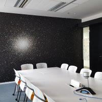 Laminovaná fototapeta s černým pozadím a motivem galaxie, nalepená na zdi zasedací místnosti, bílý konferenční stůl a židle, skleněná příčka polepená pískovanou folií s řezanou grafikou ve tvaru souhvězdí