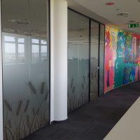 Fototapeta potištěná barevným popartovým motivem nalepená na stěně chodby, skleněné příčky s pískovanou folií s motivy obilí