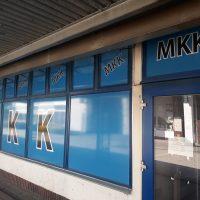 Značení výlohy MKK, skleněné tabule polepené modrou folií s černobílými písmeny, skleněné dveře