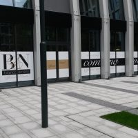Potištěná folie nalepená na skleněných tabulích mezi kovovými příčkami, reklama na moderní budově, šedá dlažba, roh umělého trávníku