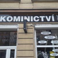 Označení výlohy Kominictví, černá folie s bílým textem na fasádě budovy, vyřezávaný text na skleněných oknech, černá reklamní výstrč s polepem