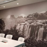 Laminovaná fototapeta s černobílou fotografií krajiny s vodopády, nalepená na stěně zasedací místnosti, bílý konferenční stůl a židle
