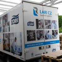 Zezadu vyfocená bílá nákladní skříň vozidla, na skříni modré polepy, loga firem LARI CZ a TORK, fotky využití produktů, v exteriéru, pod prosklenou sktřechou