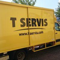 Z boku vyfocené žluté nákladní vozidlo, na skříni vozidla velký černý nápis T SERVIS a webová stránka www.tservis.com, v exteriéru na parkovišti