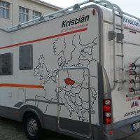 Ze zadního levého rohu vyfocené bílé obytné auto, na levém boku polep mapy Evropy v černých obrysech, ČR vybarvena červenou barvu a zvýrazněna bodem Prague, naoře vpravo logo Kristián černo-červené, v dolní i horní části šedo-oranžové pruhy, logo kristián i na zadní straně, v pozadá budova vpravo a vlevo tráva a dodávka