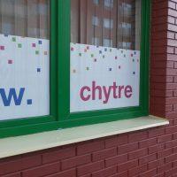 Potištěná děrovaná samolepicí reklamní folie nalepená na spodní části oken, zelené rámy, cihlová budova