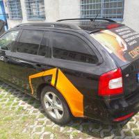 Ze zadního levého boku vyfocené černé osobní auto, na dveřích u řidiče bílý nápis, na blatníku nad zadním kolem oranžový polep, na zadním skle reklamní plocha - vlevo ruka držící stavařskou helmu, vpravo bílé nápisy, dole oranžový, v exteriéru, před domem