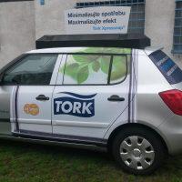 Zboku vyfocené osobní auto, přes zadná dveře včetně okna a spodní část předních dveří bílý polep, přes okno lístky, v dolní části modré logo TORK, sklo kufru také polepeno modrou barvou s bílými nápisy, na autě reklamní nástavba bílé barvy s tmavými nápisy Minimalizujte spotřebu, Maximalizujte efekt, V exteriéru, v pozadí budova