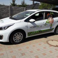 Bílé osobní auto vyfocené zboku, v dolní části obou dveří zeleno-šedý polep, na zadních dveřích polep panáčka s listy kolem hlavy, na předních dveřích šedo-zelený nápis HOBBYTEC.cz