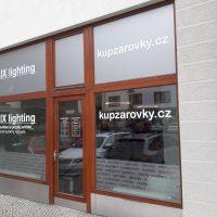 Výloha ALUX ligthing polepená pískovou folií s bílými nápisy, vyřezané texty na skleněných tabulích mezi dřevěnými rámy