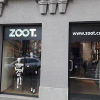 Polep výlohy a dveří ZOOT, černá folie s bílými nápisy, dámská a pánská figurína za sklem, šedá fasáda