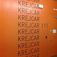Několikanásobný černý nápis KREJCAR na oranžové stěně, barevná plotrová folie
