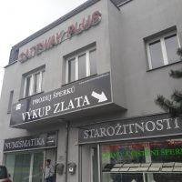 Černé folie nalepené na šedé fasádě budovy, bílé reklamní nápisy a šipka, 3D červené logo GATEWAY PLUS na budově