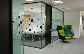 Skleněné příčky tvořící zasedací místnost v v kancelářské budově, polep pískovanou folií s modrými kruhy, šedý koberec, černo zelené křeslo