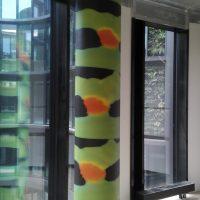 Sloup v interiéru polepený fototapetou s černo-zeleno-oranžovým abstraktním motivem, skleněná okna s výhledem na moderní budovu