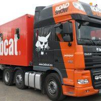 Z levého předního rohu vyfocený kamion, tahač černo-oranžový s bílými a černými nápisy a motivem šelmy, na tahači červená plocha s mohutným bílým logem Bobcat a motivem šelmy, vzadu fotka, v pozadí napravo další kamion, nalevo tráva