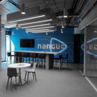 3D světelné logo Nangu TV instalované na modré fototapetě s geometrickými motivy, televize, barový stolek s židlemi, kulaté stolky s židlemi, šedá podlaha, industriální stropní osvětlení