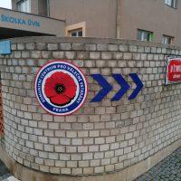 Logo Komunitního centra pro válečné veterány s trojitou šipkou jako označení směru, instalované na rohu cihlového oplocení, v pozadí budova ozančená jako ŠKOLKA ÚVN, na plotu dvě smaltové cedule s názvy ulic