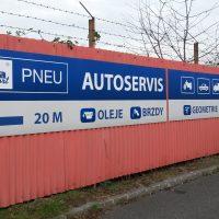 Tři podlouhlé obdélníkové reklamní cedule Autoservisu s informačním značením a piktogramy, instalované na plechovém vlnitém oplocení, ostnaté dráty, opadané stromy