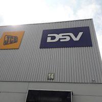 Dvě reklamní desky s logy JCB a DSV, instalované na kovové budově, pohled zespoda, v pozadí obloha s mraky