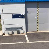Značení vjezdu do budovy pomocí modré desky s bílým značením, kovové dveře, modrá střecha, před budovou silnice s bílými pruhy