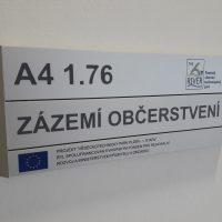 Dveřní štítek ze tří modulů, označení ZÁZEMÍ OBČERSTVENÍ Pražského vědecko technologického parku, přišroubováno na bílé stěně