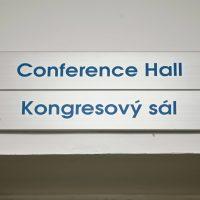 Dva informační kovové štítky nad sebou, modré nápisy Conference Hall a Kongresový sál, přišroubované na bílé zdi, pohled zespodu
